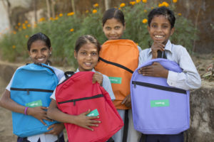 Four children holding their colourful backpacks