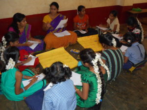 Group of young girls in India sitting indoors on the floor, using papers for an activity.