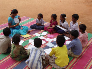 Woman and group of children sitting on the ground reading books and papers.