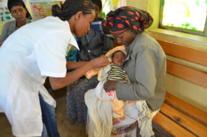 A mother holds her child in Ethiopia, waiting for the baby to be weighed.