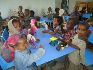 Children learn to socialize while playing with toys together, as part of the Community Caring for Children Programme.