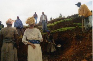Men and women of the village join together to begin digging the area to prepare the foundations of the water spring