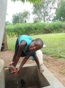 A smile on Scovia's face, who is now able to access clean and safe water in Uganda