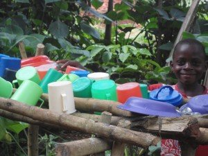 Clean dishes washed with clean water drying on racks in Uganda.