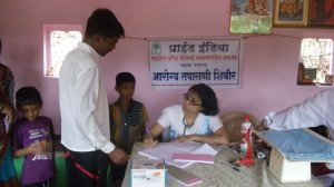 A doctor sees patients during a health camp organized by Pride India in the district of Raigad.