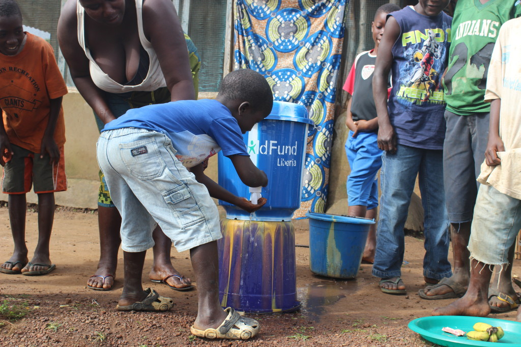 Ebola-Child-in-Liberia-washing-hands-using-ChildFund-supplied-water-dispense