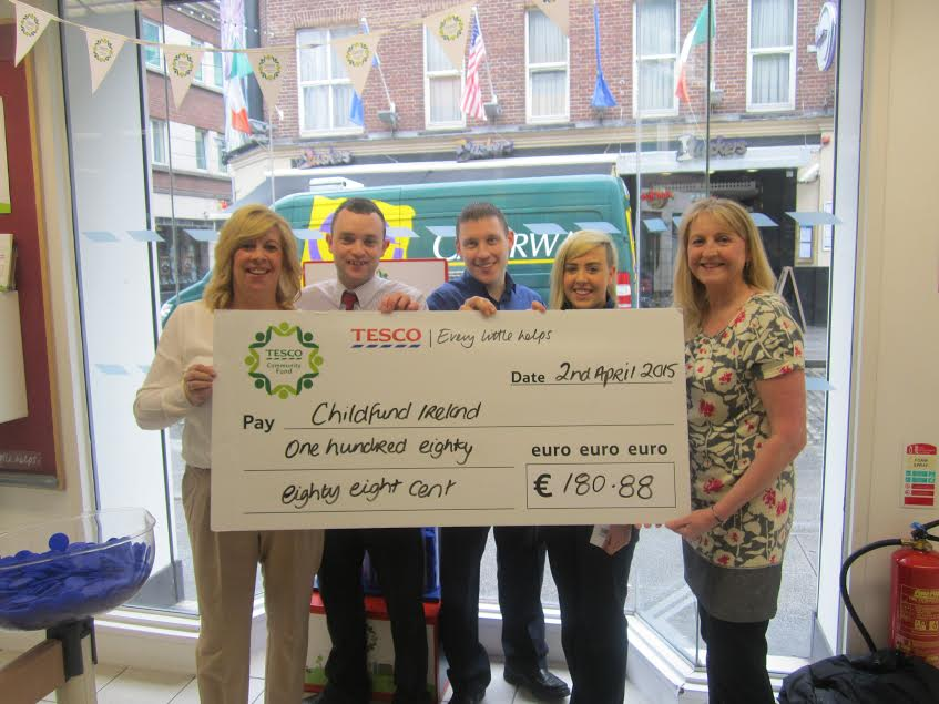 Fiona Regan of ChildFund  receiving cheque from staff at Tesco, Fleet St, Dublin