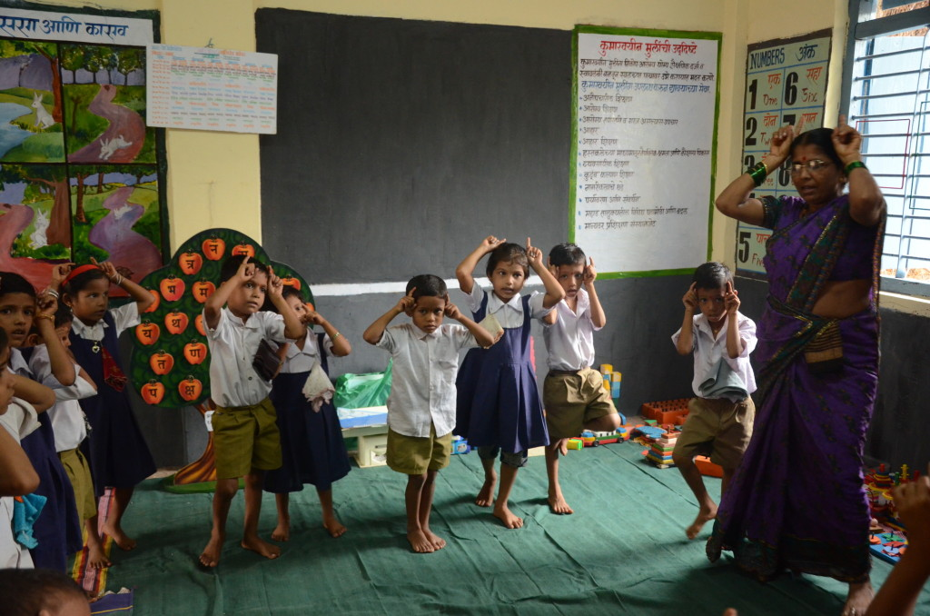 Tutor Shanta Ghatge and children acting on a story at an ECD centre in Raigad district of India's Maharashtra State.