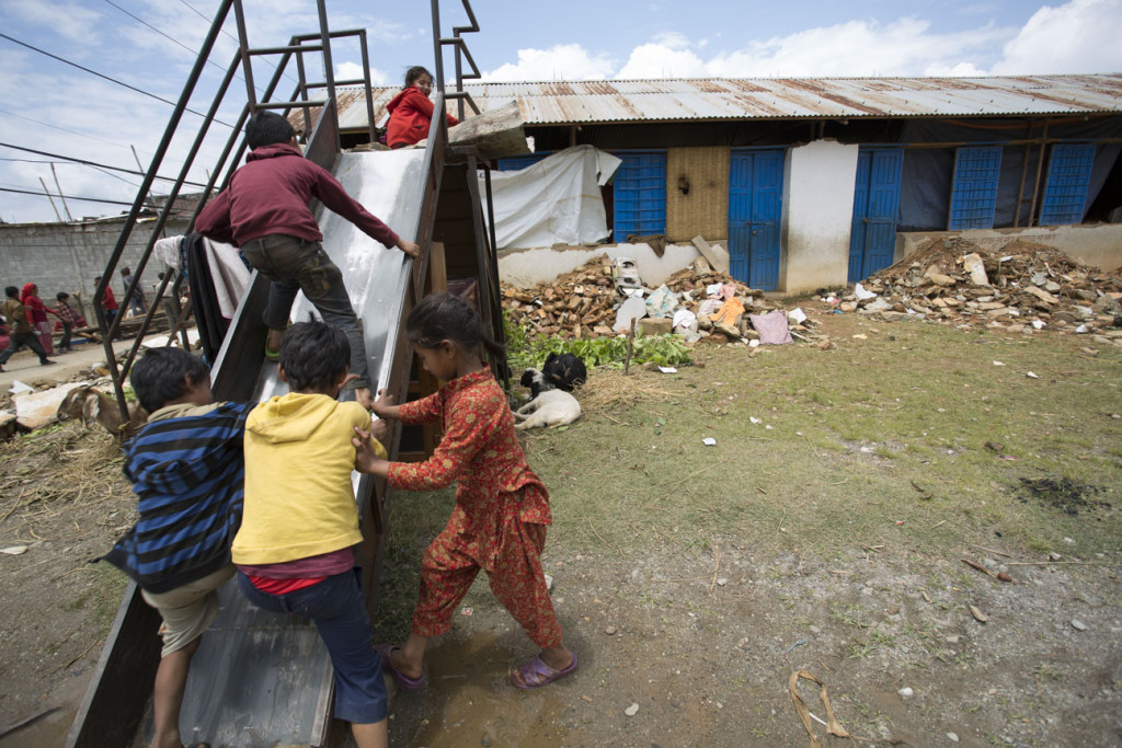 Children playing among debris in the Sindhupalchok District [Credit: Jake Lyell/ChildFund]