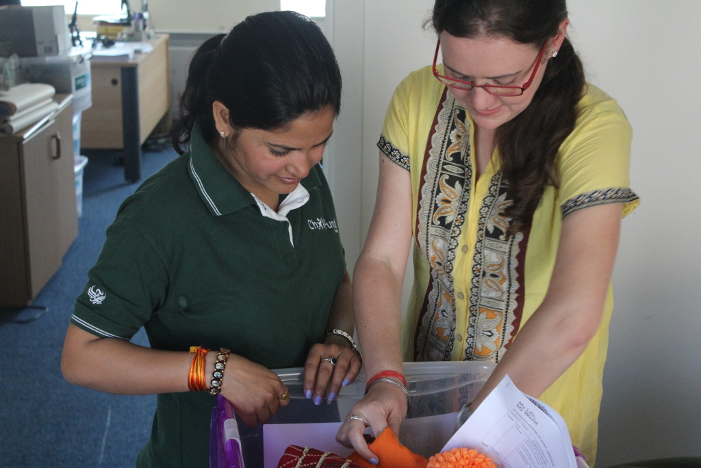 Ber & Sara examine a box of resources From India - used as part of our development education programme for school kids