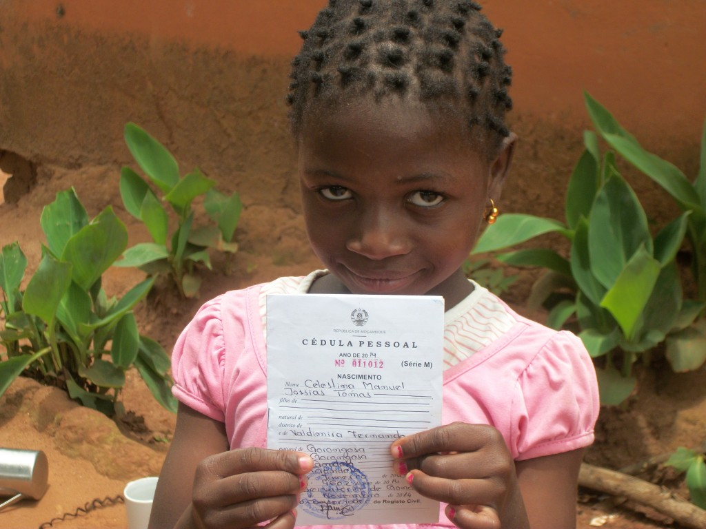 Here I am! A smiling Celestina proudly displays her Birth Registration Certificate