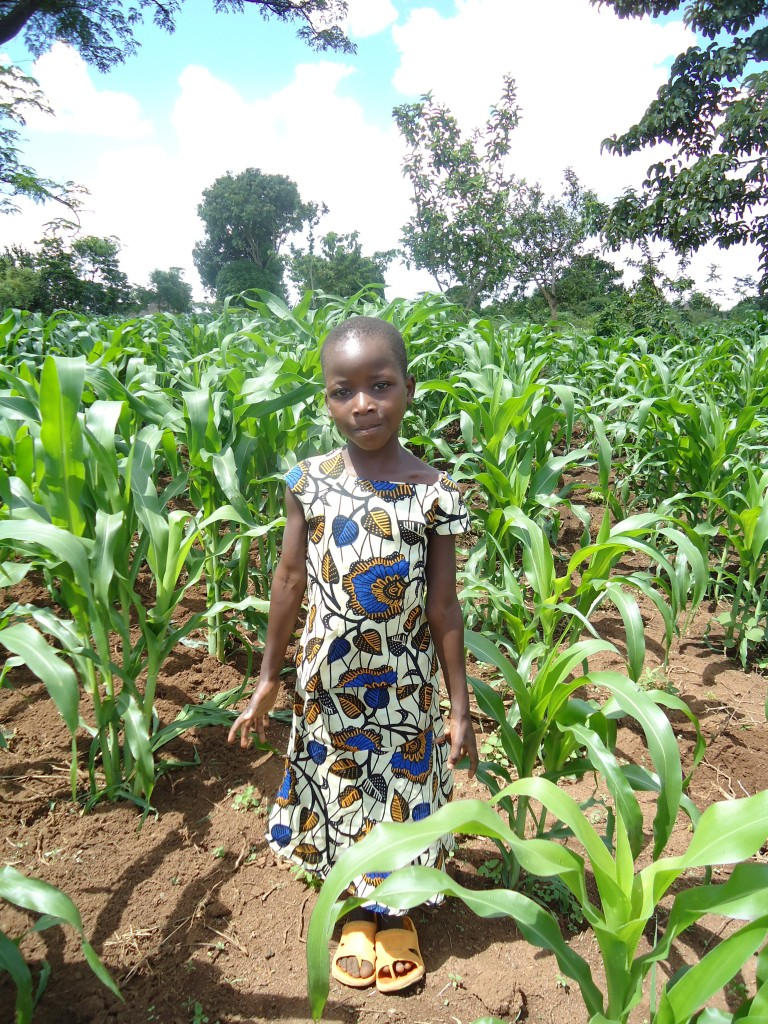 Jesca standing in her family's maize garden
