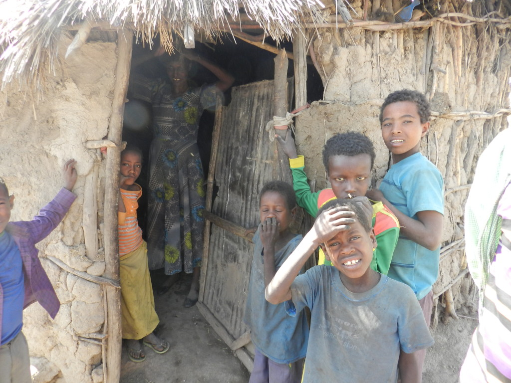 "We lost our crops and water because of shortage of rain which has brought food crises and with no water to drink..... Life is very hard! Caption: Sequare looks out from her home at six of her seven children, four of whom are in school. She says, ""We are concerned about the nutrition of our children; it is not like before when they were getting dairy products and other nutritional foods. They eat less and have very limited access to nutritional foods. Our only hope is the government and ChildFund to save our childrenâs lives."" tag = children standing outdoors, group, woman indoors looking out, quote"