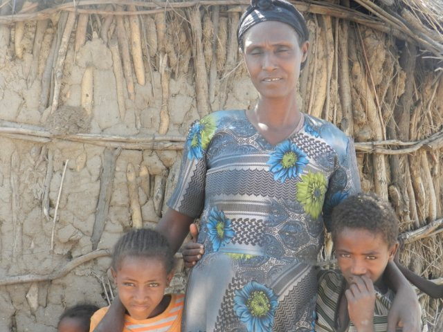 "We lost our crops and water because of shortage of rain which has brought food crises and with no water to drink..... Life is very hard! Caption: Sequare stands with two of her seven children at their home in Boset, Ethiopia. ""We are farmers and depend on agriculture, but life seems to have turned its face against us. Our only hope is the government and ChildFund to save our childrenâs lives.â tag= mother and two children standing outdoors, quote"