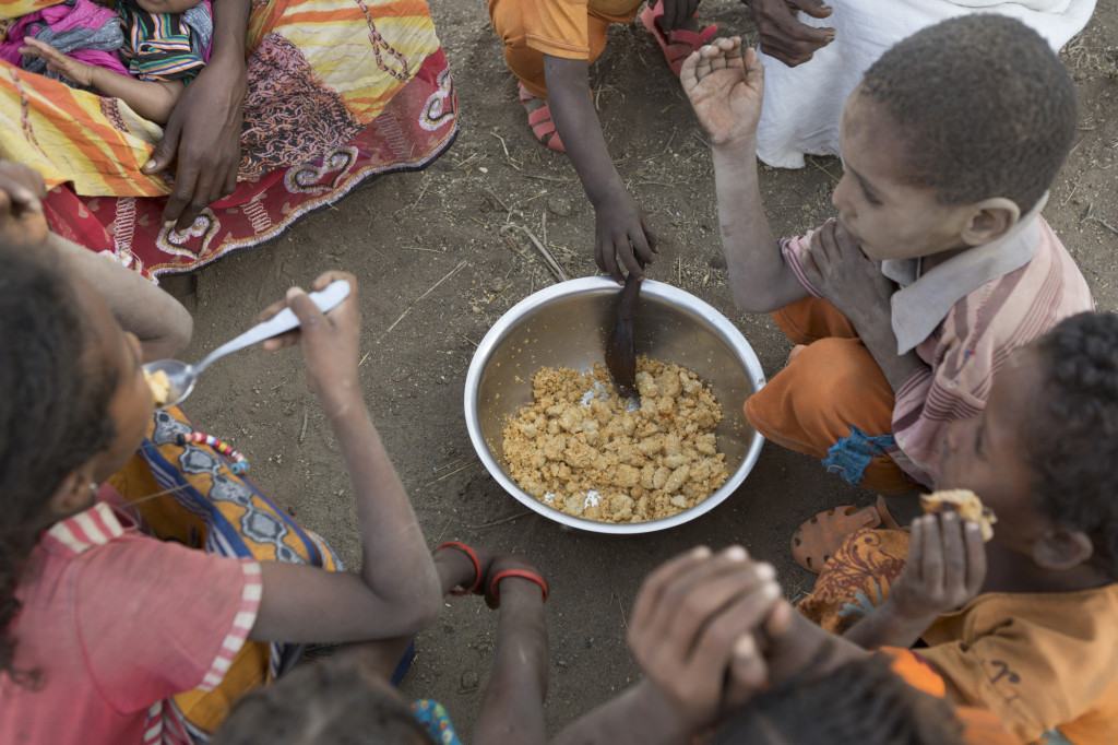 Children in a village in the Fentale District of Ethiopia share a meal of fried maize flour. Maize has been the only food this family has had access to in the past several months because of a severe drought following two years without adequate rainfall. tag = group children sitting outdoors on ground eating food from bowl spoons  Original: Members of Halko Giloâs extended family share a meager meal of fried maize flour. Maize has been the only food the family has had access to in the past several months. .Ethiopia Food Crisis - Fentale District, Ethiopia December 3, 2015.