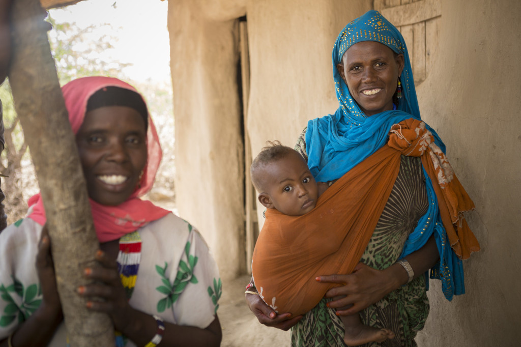 Caption: Hindi brings her eight-month-old son Jamal to an early childhood development center in the Fentale District of Ethiopia. Photo by Jake Lyell. tag = two women mother and son woman standing outdoors holding son on hip in orange wrap Original: Hindi Aliji (30) brings her young son Jamal (8 months) to an ECD centre in Fentale District, Ethiopia Ethiopia Food Crisis - Fentale District, Ethiopia December 4, 2015. Photo by Jake Lyell.