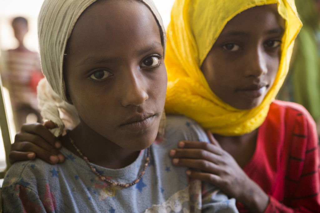 Caption: Alfiya and Ayisha, 10, stand outside a ChildFund supported health center in Koto Baloso, Ethiopia. Photo by Jake Lyell. tag = two girls outdoors arm in arm yellow white hands on shoulders Original: Alfiya (10, left) and Ayisha (10, right) stand outside a ChildFund-funded health center in Koto Baloso, Ethiopia Ethiopia - February 1, 2014.ChildFund, International - Photo by Jake Lyell.
