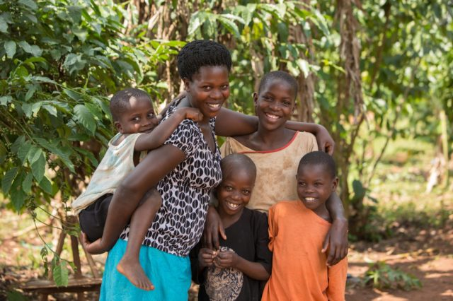 Ruth stands with her children, Alex 5, Jonathan 7, Eva, 11 and George 9, outside their home in Kamuli, Uganda. Ruth was recently reunited with her children through ChildFund's DOVCU scheme for vulnerable children. Photo by Jake Lyell.