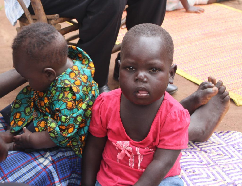 Salva with his sister, outside their family home near Kigumba, Uganda